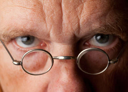 Portrait of a senior male with the focus on magnifying glasses and the eyes are blurred to suggest poor vision photo