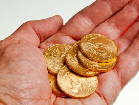 Gold Eagle one ounce coins in a stack in the palm of a hand