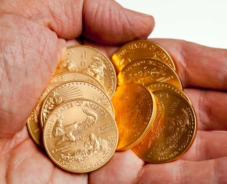 ounce: Gold Eagle one ounce coins in a stack in the palm of a hand