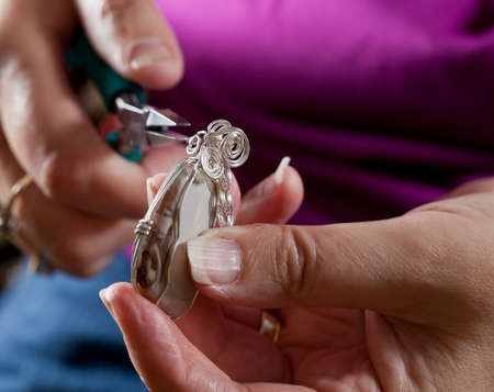 jewelry design: Hands holding pliers creating silver wire wrap pendant Stock Photo