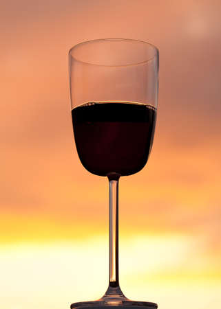 Relaxing with a glass of red wine set against the glowing orange of a brilliant sunset