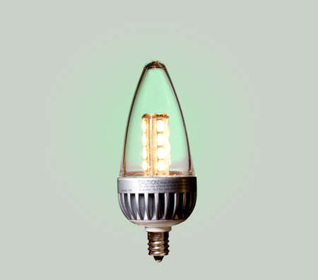 Illuminated LED bulb set against green ecological background with paths of main components included photo