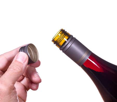 赤やワインのスクリュー トップ ボトル ボトルの首によってキャップを持っている手と白に対して分離でバラのワイン