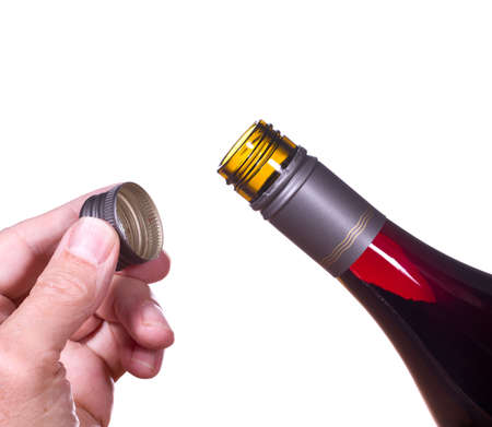 screw: Red or rose wine in screw top wine bottle  isolated against white with hand holding the cap by the neck of bottle