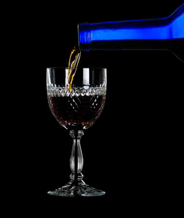 cutglass: Sherry, port or whisky being poured from blue wine bottle into an elegant cut glass and isolated against black Stock Photo