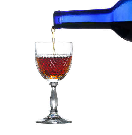 cutglass: Sherry, port or whisky being poured from blue wine bottle into an elegant cut glass and isolated against white
