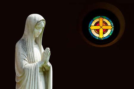virgen maria: Imagen de la Virgen rezando en el perfil con la ruta de forma aislada y fuera de foco en forma de cruz en la ventana de la derecha