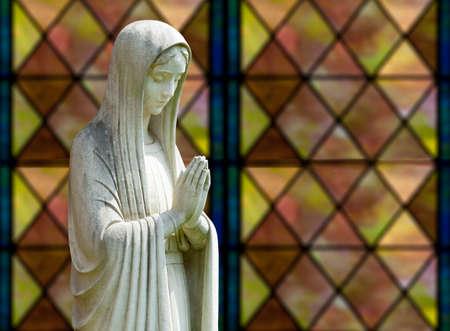 Socha Panny Marie se modlí v profilu s izolačním cestě a rozostřený okna jako pozadí