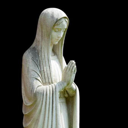 vierge marie: Statue de Marie en prière dans le profil avec le chemin de l'isolement et isolé contre le noir Banque d'images