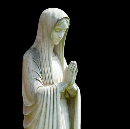 virgin: Statue of Mary praying in profile with isolation path and isolated against black Stock Photo