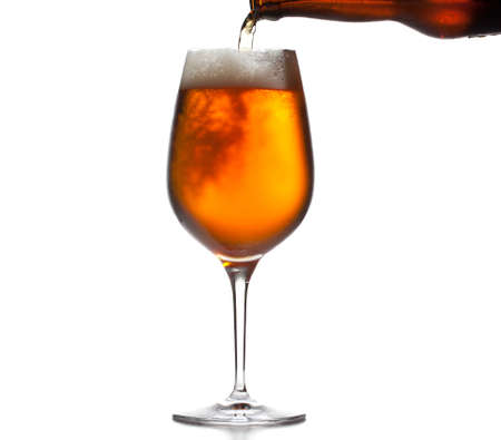 Chilled isolated beer goblet with small droplets of condensation on the outside of the glass and filled with golden colored beer being poured from brown bottle photo