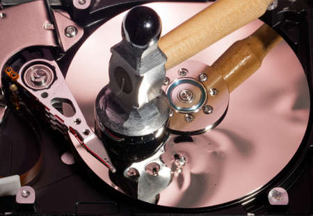 Magnetic disc inside a computer hd unit showing damage to the mirror surface of the magnetic discs and read write head from a hammer photo