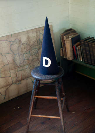 schoolhouse: Dunce cap standing on a stool in an old schoolhouse Stock Photo