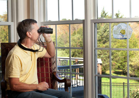 bird feeder: Senior man watching chickadee bird on birdfeeder through binoculars from chair