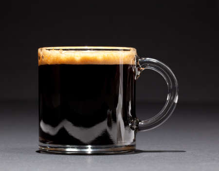 expresso: Black expresso coffee with heady froth in a glass mug or cup