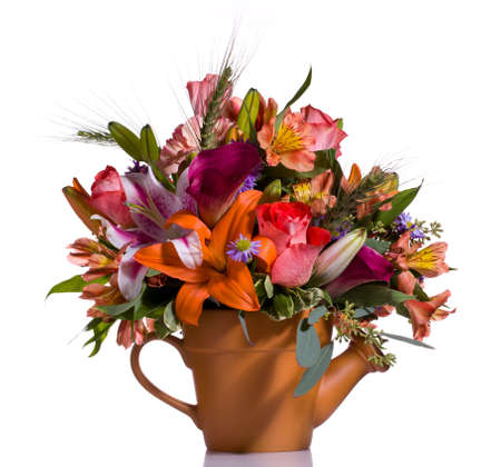 Bright and colorful bunch of flowers arranged in a watering can plant pot photo