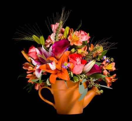 Bright and colorful bunch of flowers arranged in a watering can plant pot and isolated against black photo