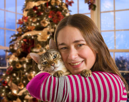 Young bengal kitten held on arm of young woman in front of brightly lit christmas tree photo