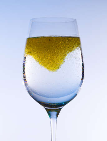 Olive oil being stirred in a large wine goblet forming golden bubbles in the liquid photo