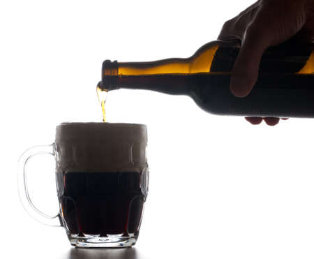 ipa: Backlit isolated beer tankard with dark ale being poured from brown bottle and creating a large head of froth on the liquid
