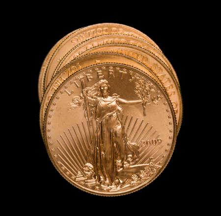 lingotes de oro: Gold Eagle monedas de un onza en una pila y aislada contra el negro