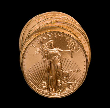 Gold Eagle one ounce coins in a stack and isolated against black Imagens