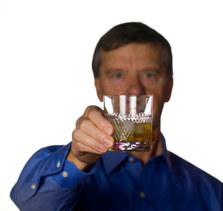 Senior retired male with a glass of scotch whiskey on ice in a cut glass with the man out of focus photo