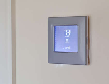 Electronic thermostat with blue LCD screen for controlling air conditioning and heating HVAC Stock Photo