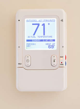 temperature controller: Electronic thermostat with blue LCD screen for controlling air conditioning and heating HVAC Stock Photo