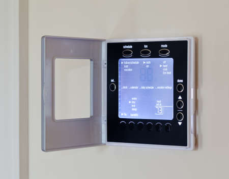 panel: Electronic thermostat with blue LCD screen for controlling air conditioning and heating HVAC Stock Photo