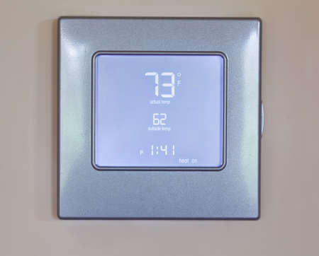 by the lcd screen: Electronic thermostat with blue LCD screen for controlling air conditioning and heating HVAC Stock Photo