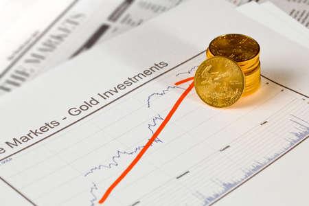 lingotes de oro: Gold Eagle monedas de una onza apiladas en el gráfico de los precios del oro en las páginas de negocios del periódico con los gráficos que muestran un aumento en el valor