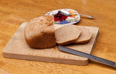 Slices of home made wheat bread on breadboard with knife photo