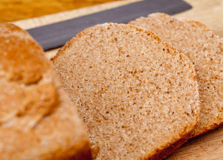 slicing: Slices of home made wheat bread on breadboard with knife