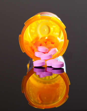 Set of round purple tablets pouring from an orange pill bottle photo