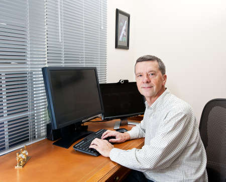 Senior executive in home office with two monitors and keyboard on leather desk and facing the camera Stock Photo - 11526509