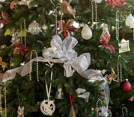 Christmas tree decorated with silver and white ribbons and ornaments in family home Stock Photo - 11526594