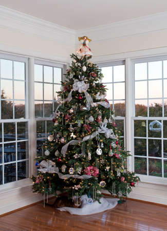 Christmas tree decorated with silver and white ribbons and ornaments in family home photo