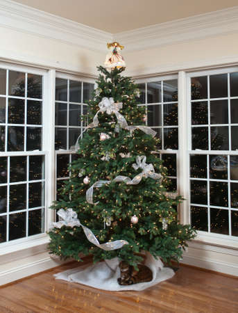 Christmas tree decorated with silver and white ribbons and ornaments in family home Stock Photo - 11526593