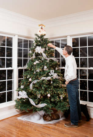Senior man decorating a Christmas tree in family home Stock Photo - 11526549