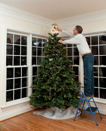 decorating christmas tree: Senior man decorating a Christmas tree in family home
