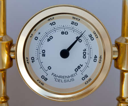 celsius: Gold thermometer measuring centigrade and farenheit and fixed in a brass holder Stock Photo