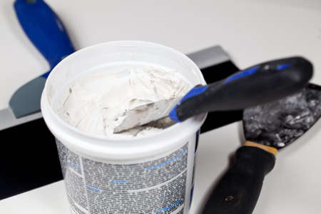 patching: Knife in patching plaster in plastic tube with other tools on the floor Stock Photo