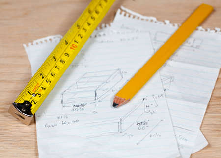 mm: Tape measure and pencil laying on plans for a woodworking project Stock Photo