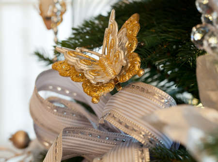 Christmas tree decorated with silver and white ribbons and butterfly ornaments in family home Stock Photo - 11526698