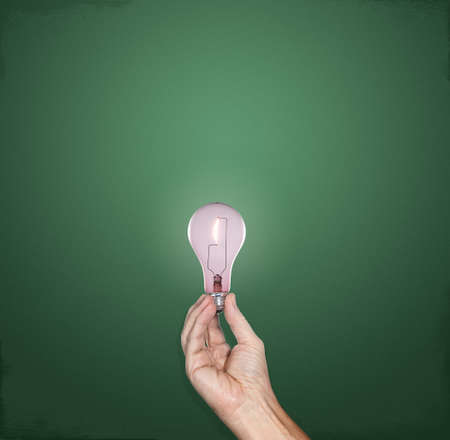 Hand holding a bright incandescent lightbulb in front of a green chalkboard with plenty of copy space photo