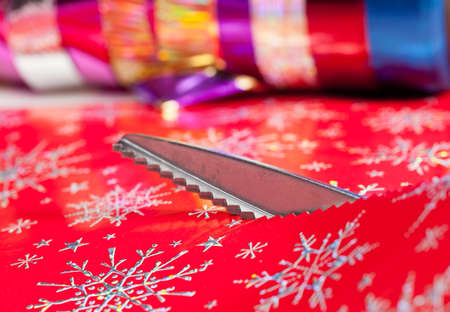Christmas paper being cut by special scissors to create pattern in the cut edge photo