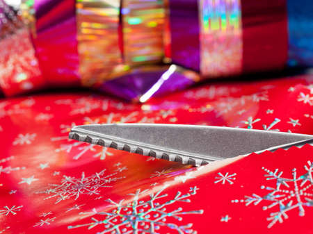 snip: Christmas paper being cut by special scissors to create pattern in the cut edge Stock Photo