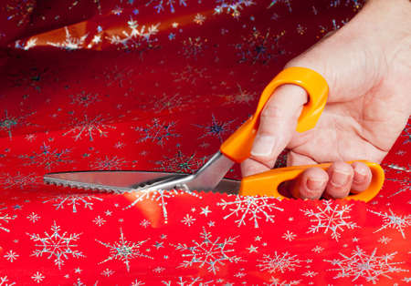 Christmas paper being cut by special scissors to create pattern in the cut edge Stok Fotoğraf