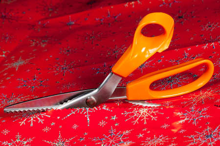 shear: Christmas paper being cut by special scissors to create pattern in the cut edge Stock Photo